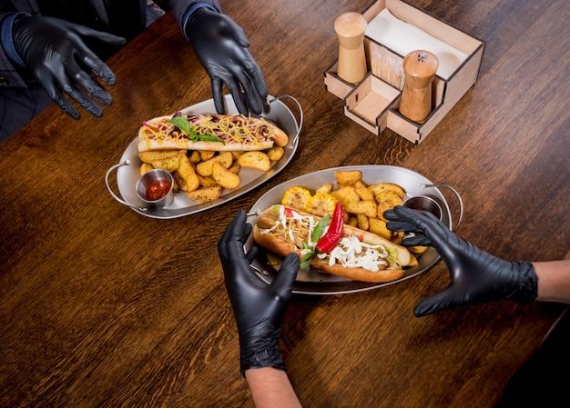 カフェでホットドッグを食べる2人の空腹の若い男性。レストラン