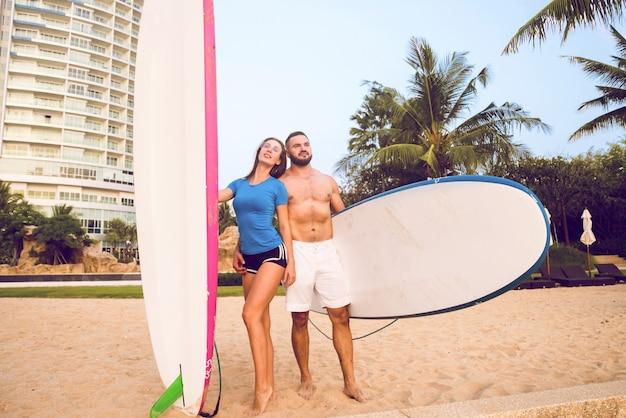 ビーチでボードを持つ2つの若いサーファー