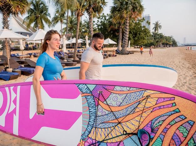 サーフボードで海に行く2人の若いサーファー