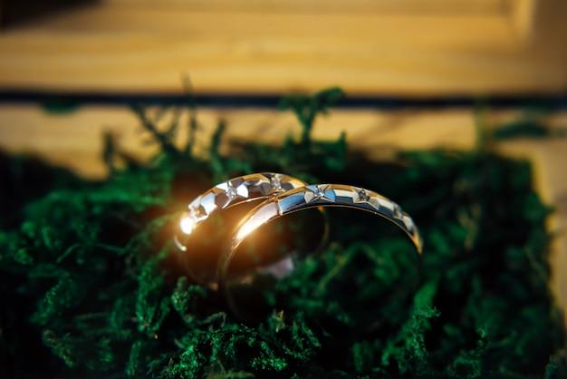 2つの輝く結婚指輪をクローズアップ。コピースペースで緑背景をぼかした写真の金の結婚指輪。
