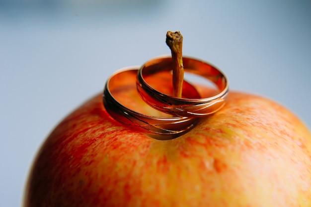 赤いリンゴの2つの金の結婚指輪クローズアップ。新郎新婦、セレクティブフォーカスのビンテージリング。