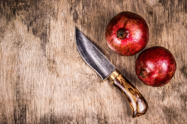2つの熟したザクロと木の板にナイフ