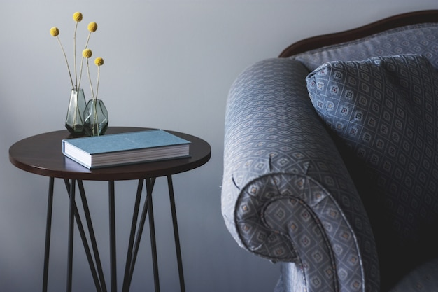 本と小さな植物が付いた小さな丸いテーブルの近くに青いソファのショットと黄色の植物が置かれた2つの花瓶