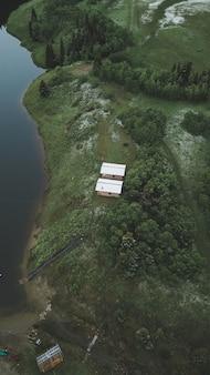 川の上の熱帯のジャングルの端にある2つのコテージの垂直ハイアングルショット