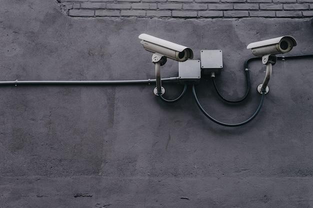灰色の壁に2つの防犯カメラ
