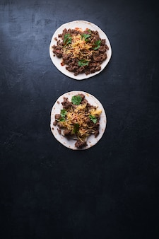 肉と黒の表面に溶けるチーズの2つのトルティーヤパンの垂直ハイアングルショット