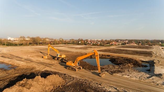 建築現場の2つの掘削機のハイアングルショット