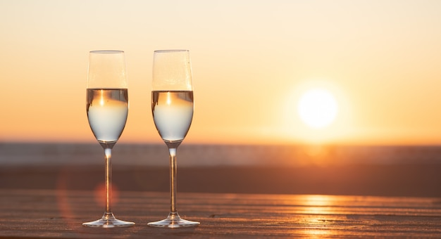 夕暮れ時のテーブルの上のシャンパンを2杯
