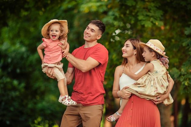 幸せな家族のお母さんお父さんと楽しい2人の娘。