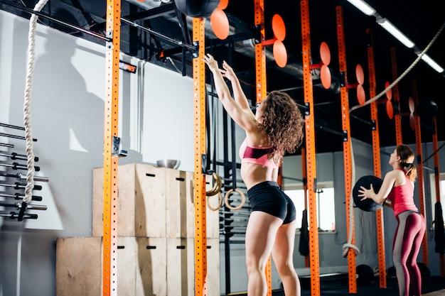 フィットネスとエクササイズのコンセプト-ジムでトレーニングメディシンボールを持つ2人の女性
