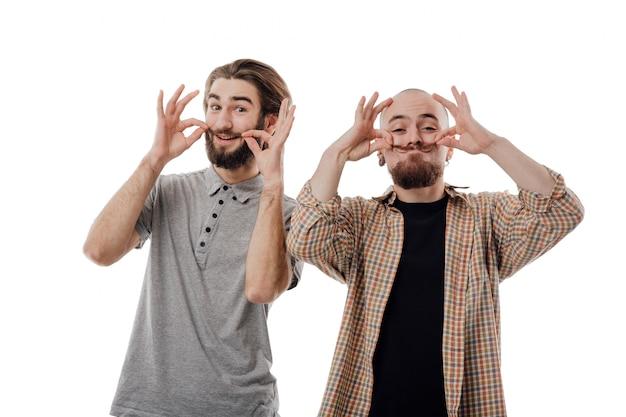 2人の若い男性と陽気な顔をゆがめたカメラを見て、口ひげ、分離されたホワイトスペース、コピースペース、分離を保持