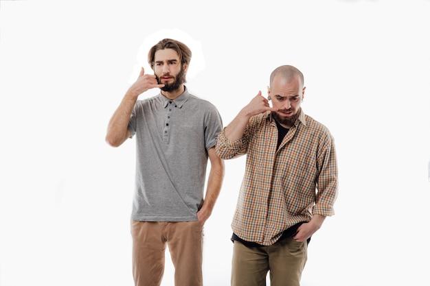 2人の男性が電話、孤立したホワイトスペース、コピースペース、孤立した電話での会話を模倣します。