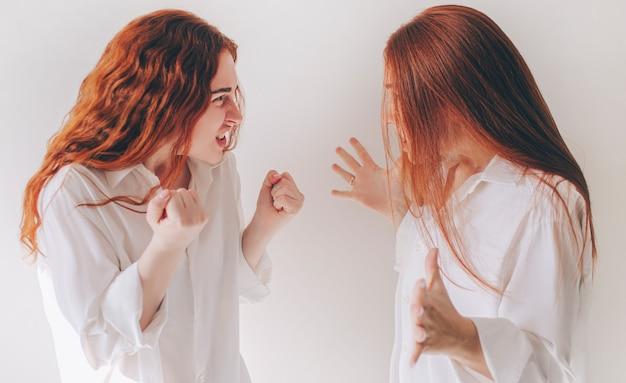 Стойка 2 рыжеволосых сестер изолированная на белой предпосылке в просторных негабаритных рубашках. две молодые женщины разозлились и кричат друг на друга. они чувствуют ярость, агрессию, гнев.
