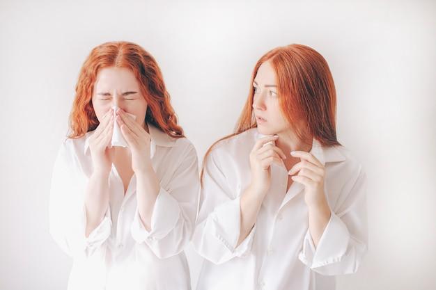 ハンカチを持つ若い女性。病気の女の子は鼻水があります。女性モデルは、白い背景の背景に分離された一般的な風邪の治療法になります。 2人目の若い女性は感染するのを恐れています