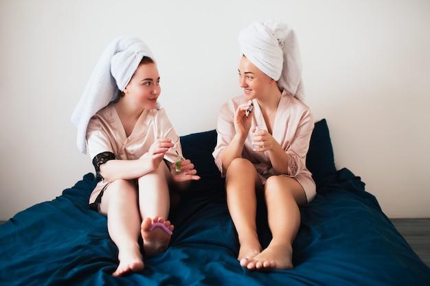 タオルとパジャマを着た2人の若い女性が家で一緒に楽しいスパパーティーをします。