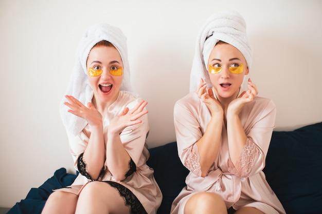 目の下のパッチを楽しんでいる2人の若い女性