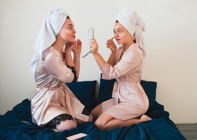 女性モデルは顔にクリームを塗ります。タオルとパジャマを着た2人の若い女性が家で一緒に楽しいスパパーティーをします。