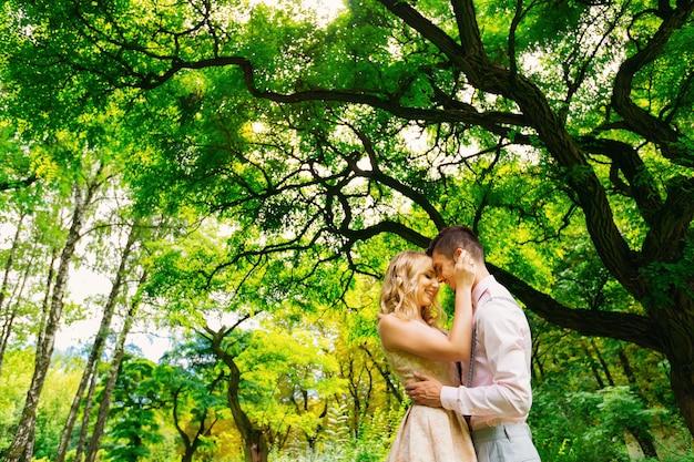 緑の木々を背景にした2人の恋人の官能的な抱擁