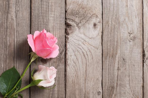 古い木製の表面に2つのピンクのバラ