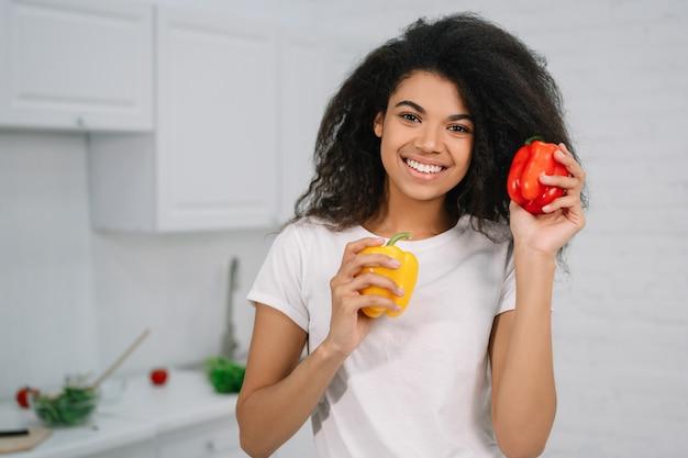 キッチンに立っている2つのピーマンの間を選択する美しい女性。野菜を持って、家で料理して幸せな主婦