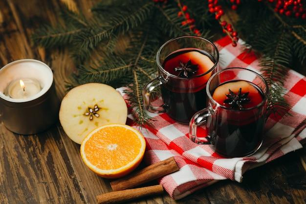 チェックされたテーブルクロスに柑橘類、リンゴ、スパイスとグリューワインを2つのガラスのコップ。