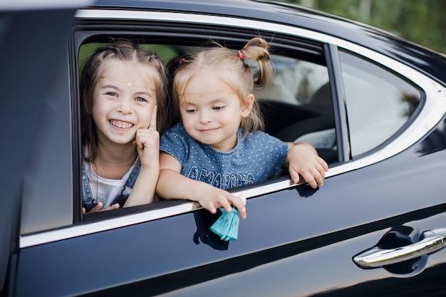 車の窓を通して見る2つの女の赤ちゃん