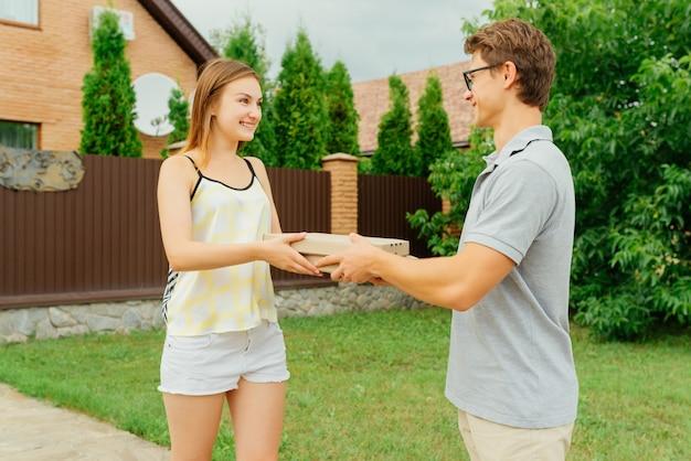 屋外の民家の近くの魅力的な女性にピザの2つのボックスを与える若い配達人。