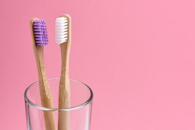 ピンクの背景のガラスに2つの竹の歯ブラシのクローズアップ。エコフレンドリーで廃棄物ゼロのコンセプト写真。