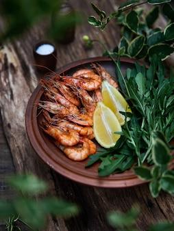 2つのレモンスライスと木の板に茶色のプレートにルッコラと揚げたエビ