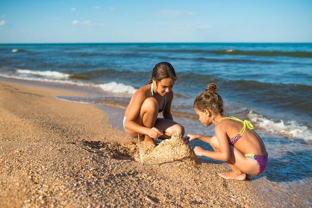 2人のかわいい妹が砂で遊ぶ