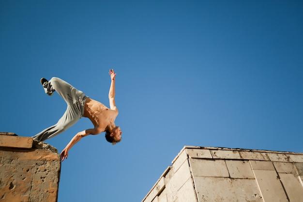 若い男がジャンプして晴れた夏の日に外の2つの建物の間でパルクールを練習