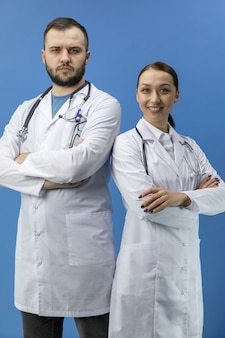 立っている2つの魅力的な医師が青い背景にカメラを見てください。