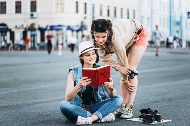 地図のある2人の美しい観光客が旧市街を歩きます
