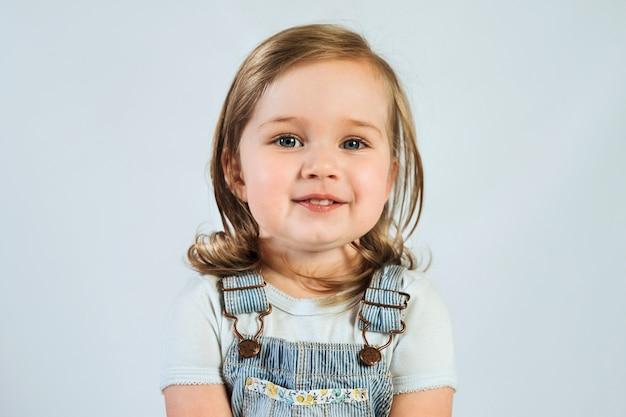 白い背景の上の2歳の幸せな笑顔の赤ちゃんの肖像画。