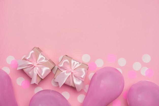 白い紙吹雪と風船のパステルピンクのテーブルにピンクのリボンの弓を持つ2つのギフトボックス