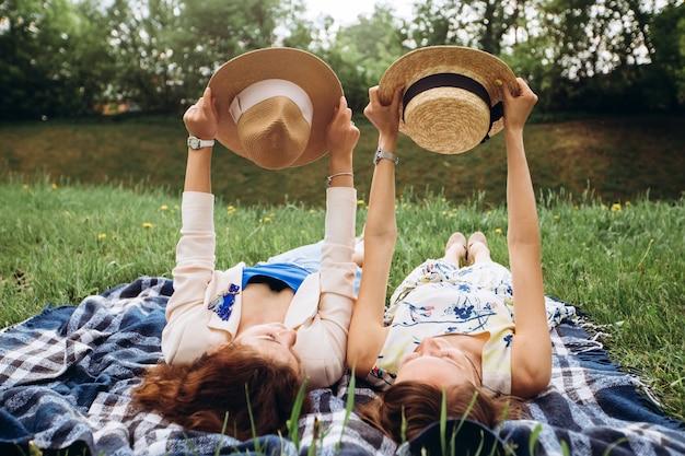 Две красивые девушки лежат на синем пледе на открытом воздухе в парке, летний пикник. девушки подружек веселятся, смеются, улыбаются и резвятся. портрет крупного плана 2 молодых женщин в платьях и соломенных шляпах.