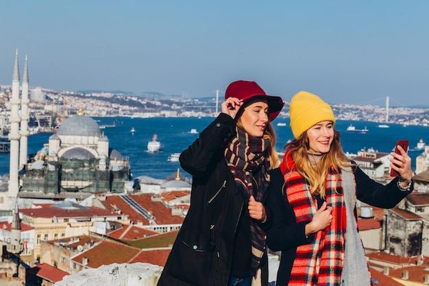 ガールフレンドは、トルコ、イスタンブールのグランドバザールの屋上で自撮りします。晴れた冬の日に、イスタンブールを背景に2人の笑顔の女の子が電話で撮影されています。