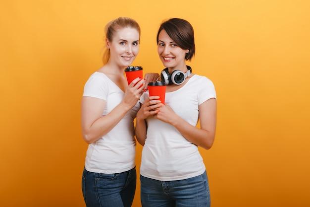 カジュアルな服を着て紙コーヒーグラスを保持している2人の女性。黄色の背景に立っています。