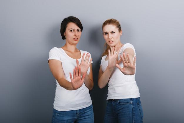反発のジェスチャーを見せて、カメラを見ている2人の女性。