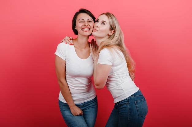 スタジオでポーズをとって幸せな傾いた頬を頬に見ている2人の女性