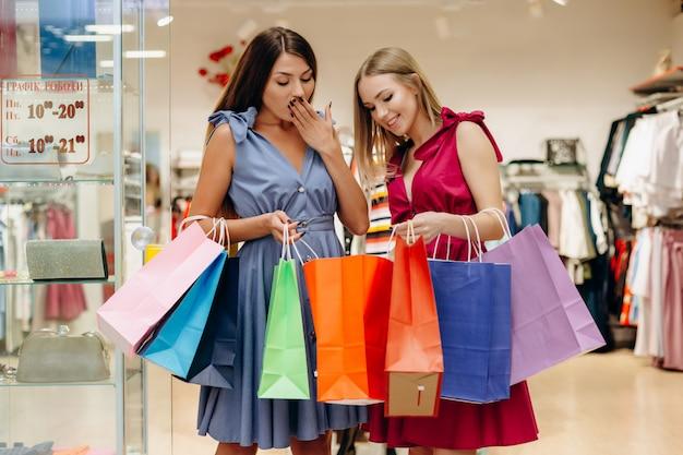 2人の若い女の子は買い物の後喜ぶ