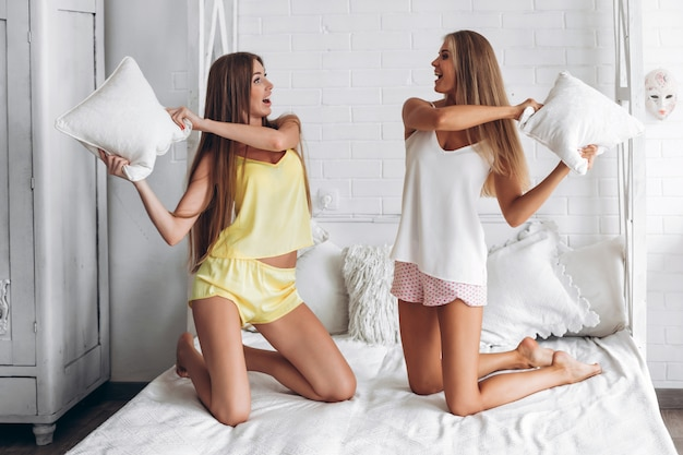 枕を持っている下着姿の2つのガールフレンドが寝室で戦う