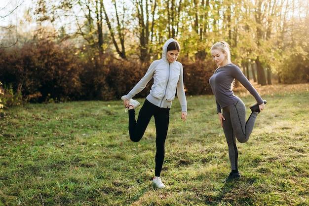 公園での朝のフィットネス。 2人の若い女の子が演習を行っています。