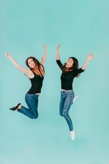 2人の陽気な女性が高いジャンプ