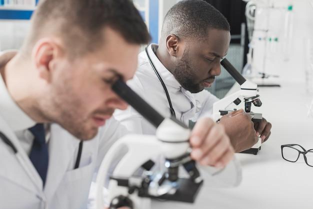 顕微鏡を見ている2人の医者