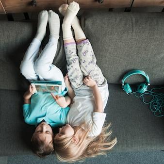 タブレットで遊ぶ2人の女の子と技術コンセプト