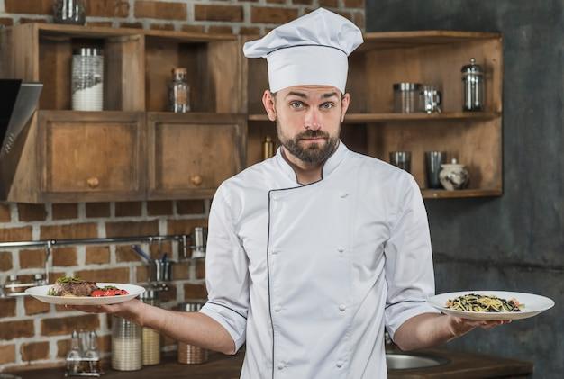 彼の手に2つの異なる料理を持っている不確かな男性シェフ