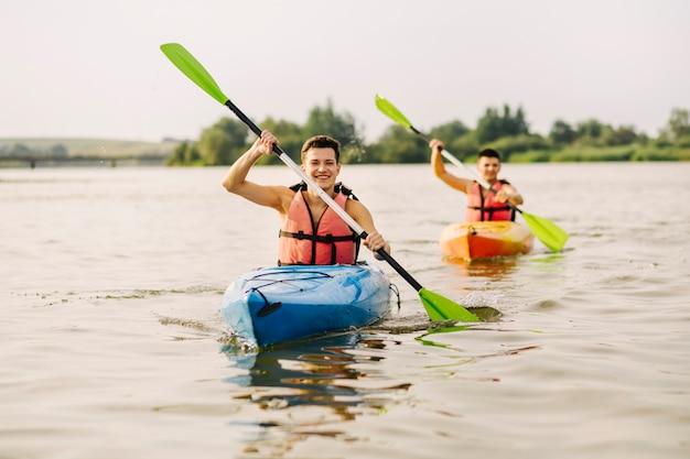 2人の男が湖でカヤックをする