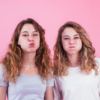ピンクの背景に頬を吹く2人の女性の友人