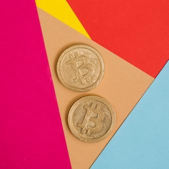 多くのカラフルな背景に2つのビットコイン